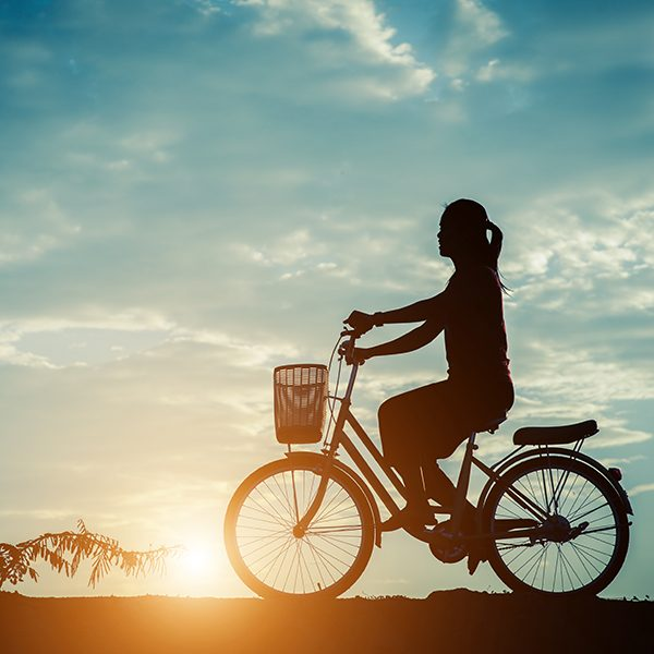 Silhouette of women with bicycle and beautiful sky